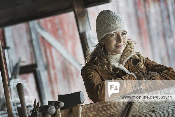 Ein Bio-Bauernhof im Hinterland von New York  im Winter. Eine Frau in einem Schafspelzmantel. Eine Reihe von Handwerkzeugen hängt an einem Pfosten.