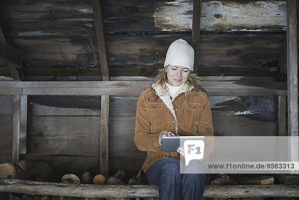 Ein Bio-Bauernhof im Hinterland von New York  im Winter. Eine Frau sitzt in einem Nebengebäude und benutzt ein digitales Tablett.