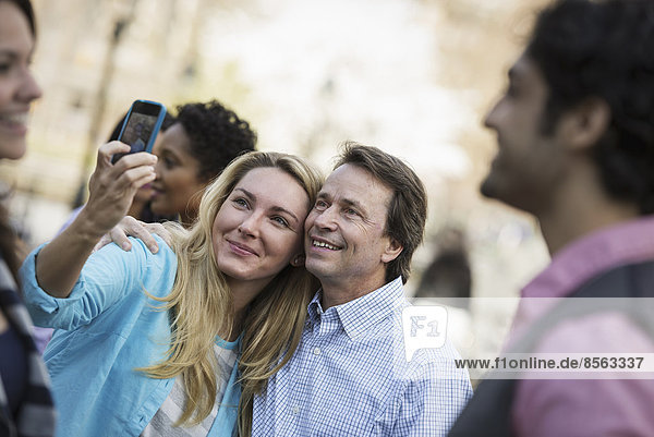 People outdoors in the city in spring time. A woman using her cell phone to take a photograph. A group of friends  men and women.