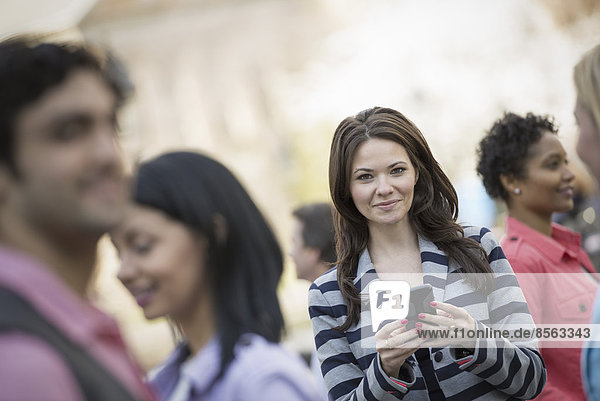 People outdoors in the city in spring time. New York City park. A young woman holding a mobile phone  and looking up at the camera.