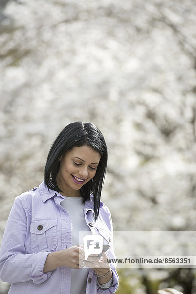 Outdoors in the city in spring time. New York City park. White blossom on the trees. A young woman checking her mobile phone and smiling.