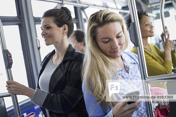 New Yorker Stadtpark. Menschen  Männer und Frauen in einem Stadtbus. Öffentliche Verkehrsmittel. In Kontakt bleiben. Eine junge Frau  die ihr Mobiltelefon überprüft oder benutzt.