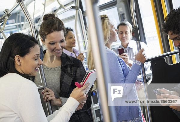 New Yorker Stadtpark. Menschen  Männer und Frauen in einem Stadtbus. Öffentliche Verkehrsmittel. Zwei Frauen betrachten ein tragbares digitales Tablet.