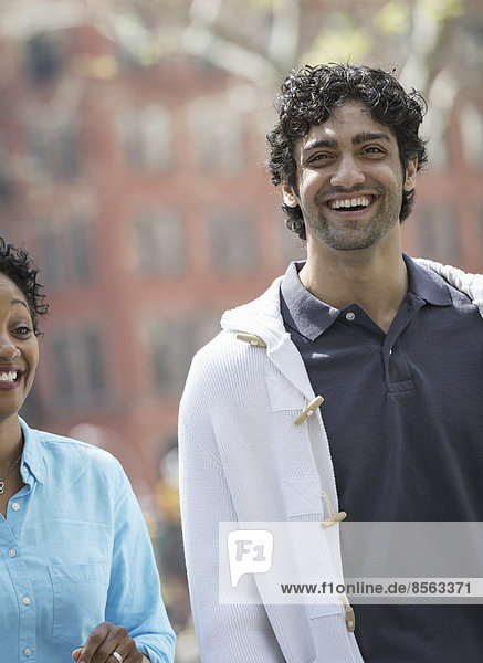 Menschen im Frühling in der Stadt im Freien. Der New Yorker Stadtpark. Ein Mann und eine Frau Seite an Seite  lächelnd.