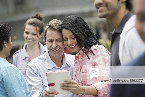Außenaufnahme  Frau  Mann  New York City  Mensch  sehen  Menschen  Menschengruppe  Menschengruppen  Gruppe  Gruppen  Großstadt  Zeit  Tablet PC  freie Natur  sichtschutz