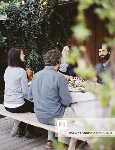 Eine Gruppe von Menschen um einen Tisch in einem Garten. Ein Festmahl mit gedecktem Tisch und Blattdekoration. Gläser  Teller und Besteck.
