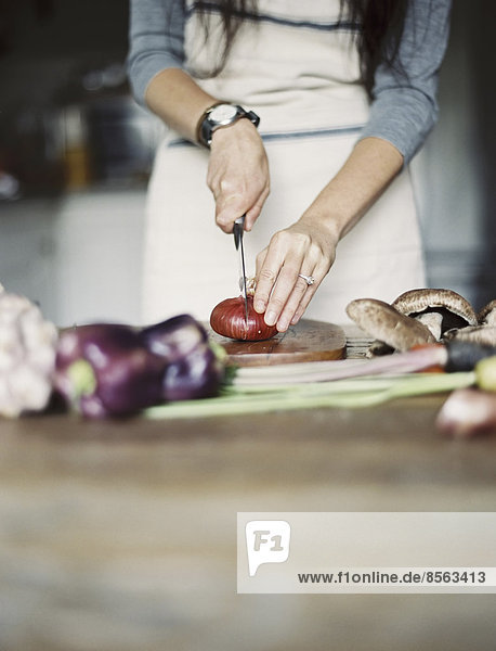 Eine häusliche Küche. Eine Tischplatte. Junge Frau  die frisches Gemüse mit einem Messer schneidet.
