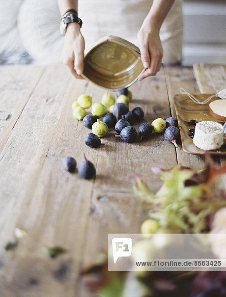 Eine Frau an einem häuslichen Küchentisch. Arrangieren von frischem Obst  schwarzen und grünen Feigen auf einer Käseplatte. Bio-Lebensmittel. Vom Bauernhof auf den Teller. Eine Frau an einem häuslichen Küchentisch. Arrangieren von frischem Obst, schwarzen und grünen Feigen auf einer Käseplatte. Bio-Lebensmittel. Vom Bauernhof auf den Teller.