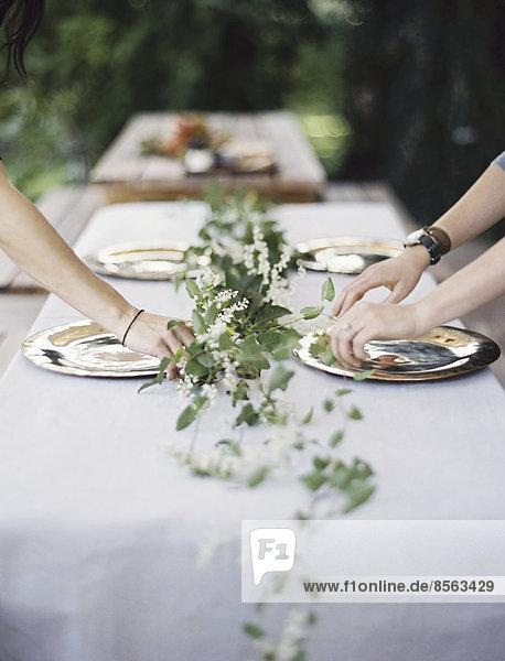 Zwei Personen lehnen sich über einen Tisch  der außen mit einem weißen Tuch und einer Tischdekoration aus Laub in der Mitte gedeckt ist. Platzieren von Besteck und Tellern auf einer Tischplatte.