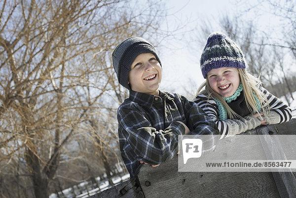 Winterlandschaft mit Schnee auf dem Boden. Zwei Kinder mit Strickmützen  die auf einem Zaun lehnen.
