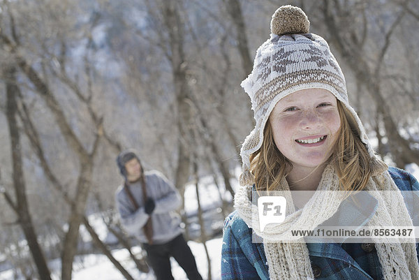 Winter scenery with snow on the ground. A young girl with a bobble hat and scarf outdoors. A man in the background.
