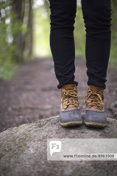 Eine Frau in Wanderstiefeln und Jeans  die auf einem Stein neben einem Waldweg steht.