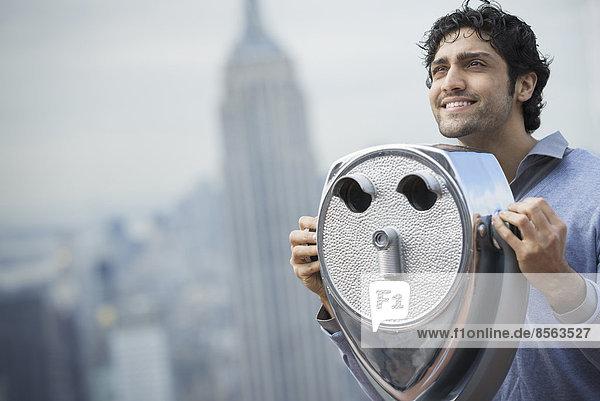 New York City. Eine Aussichtsplattform mit Blick auf das Empire State Building. Ein junger Mann blickt durch ein Teleskop über die Stadt.
