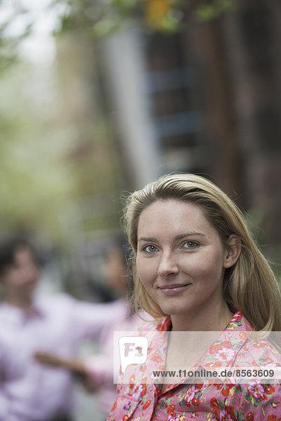 Stadtleben im Frühling. Eine Frau mit langen blonden Haaren schaut in die Kamera.