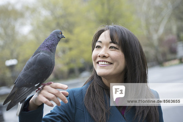 Eine junge Frau im Park mit einer Taube an ihrem Handgelenk.