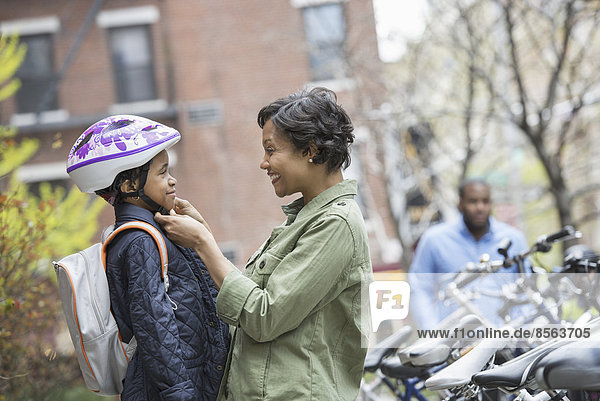 Ein New Yorker Stadtpark im Frühling. Ein Junge mit einem Fahrradhelm  der von seiner Mutter neben einem Fahrradträger befestigt wird.