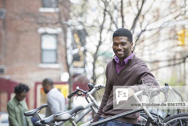 Außenaufnahme  Städtisches Motiv  Städtische Motive  Straßenszene  Straßenszene  Wäscheständer  Mann  Lifestyle  lächeln  Großstadt  Blick in die Kamera  jung  Fahrrad  Rad  freie Natur
