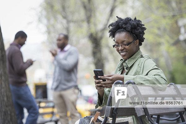 Draußen in der Stadt im Frühling. Ein urbaner Lebensstil. Eine Frau auf einer Bank  die ihr Telefon kontrolliert. Zwei Männer im Hintergrund.