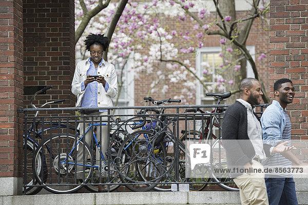 Draußen in der Stadt im Frühling. Ein urbaner Lebensstil. Ein Fahrradträger mit verschlossenen Fahrrädern  eine Frau  die SMS schreibt und zwei Männer  die vorbeigehen.