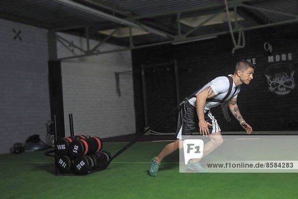 Frankreich  Mann  der in einer Crossfit-Gymnastikhalle trainiert.