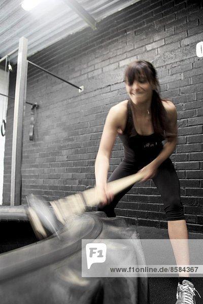 Frankreich  junge Frau mit einem Hammer in einer Crossfit-Gymnastikhalle...