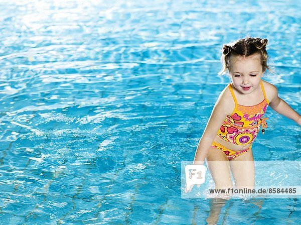 Little girl playing in water at the swimming pool