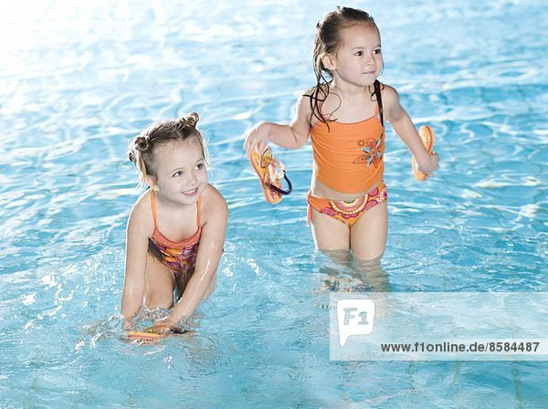 Two smiling girls at the swimming pool