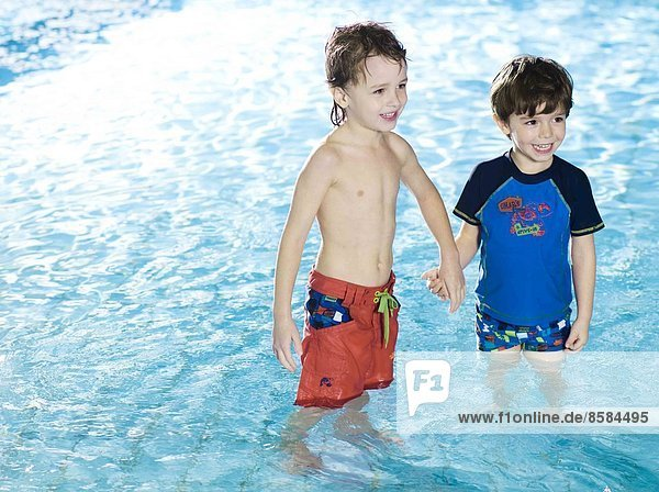 Two boys giving hands in water at the swimming pool