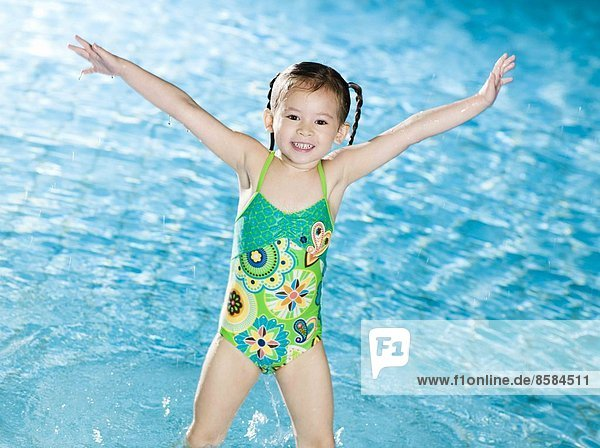 Smiling little girl posing at the swimming pool