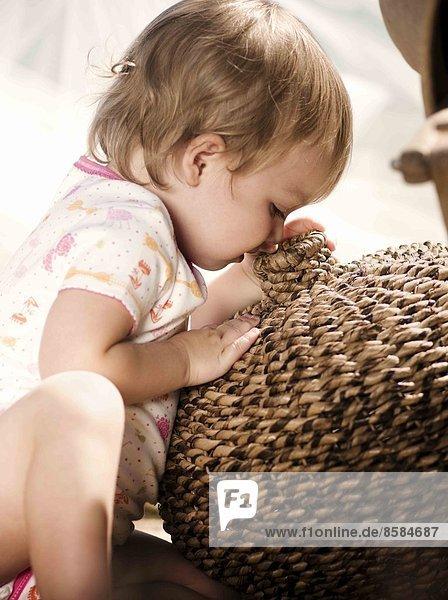 Nahaufnahme eines gesessenen Babys  das in einen Korb schaut.