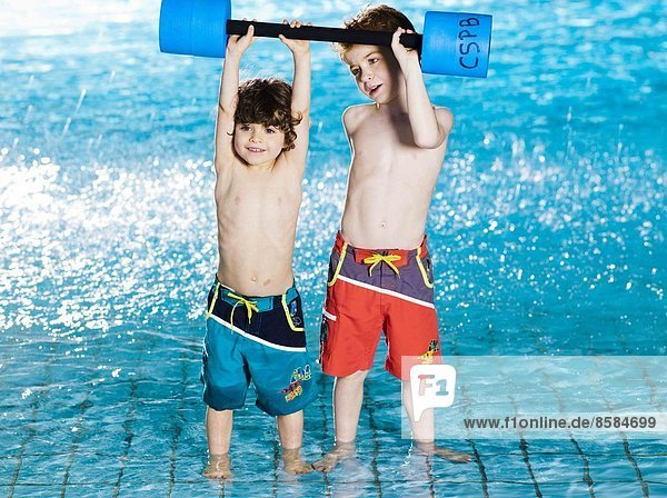 Two boys carrying foam dumbbell at the swimming pool