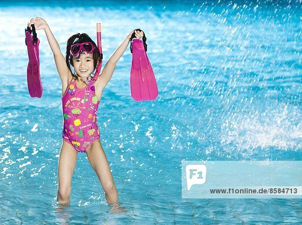 Little girl with flippers  mask and snorkel at the swimming pool
