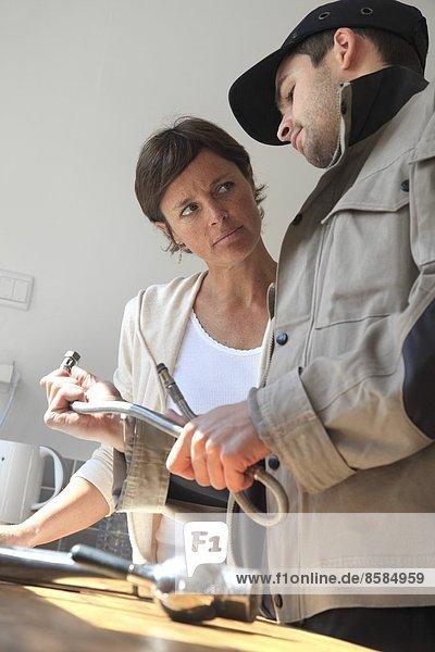 Frankreich  Klempner und Besitzer in einer Küche.