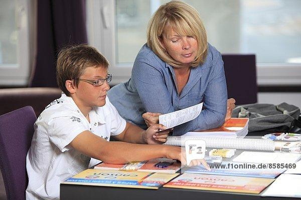 Frankreich  Junge und Mutter  Schulwerkzeug auf dem Wohnzimmertisch.