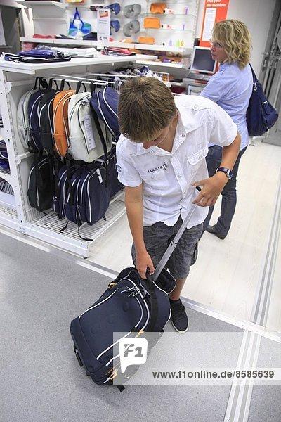 Frankreich  Schüler und seine Mutter wählen ein Portfolio in einem Supermarkt.