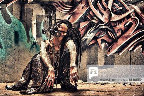 DeathWorker  ein Cyberpunk-Mann sitzt vor einer Graffiti-Wand