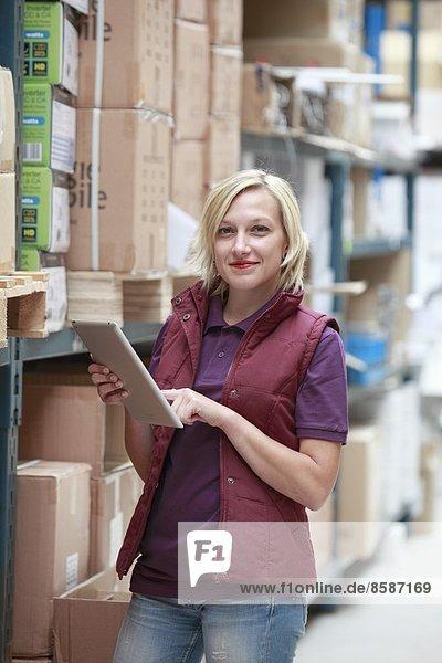 Frankreich  junge Frau mit Tablet-Computer im Lagerhaus.