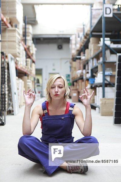 Frankreich  junge Frau  die in einem Lagerhaus arbeitet.