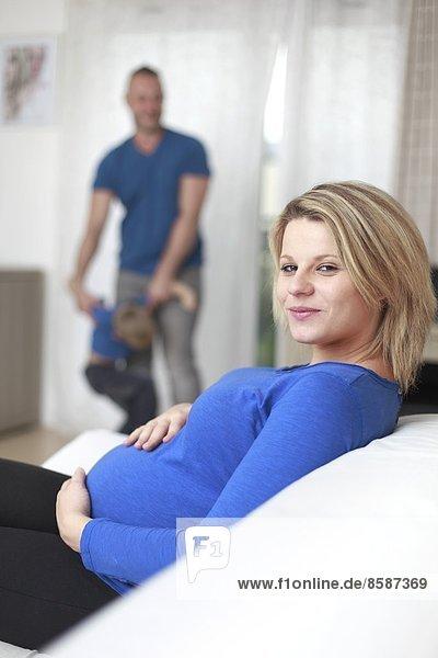 Frankreich  lächelnde Schwangere  ihr Mann und ihr Sohn im Hintergrund.