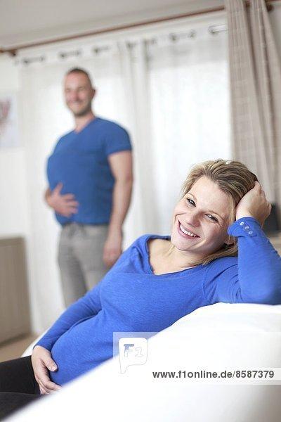 Frankreich  lächelnde Schwangere  ihr Mann im Hintergrund.