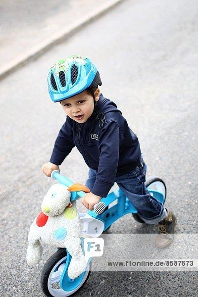 Ein kleiner Junge und sein Fahrrad auf der Straße