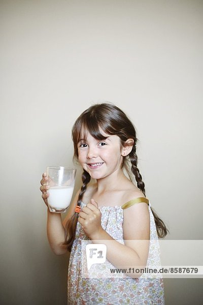A little girl with a glass of milk