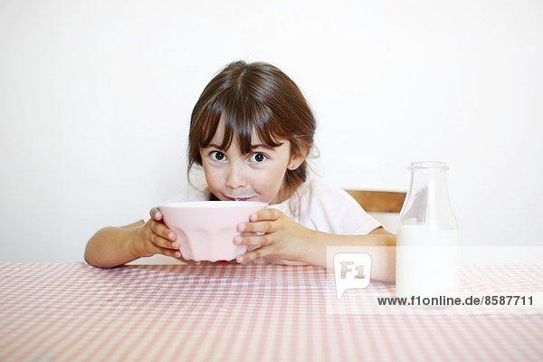 Ein kleines Mädchen sitzt an ihrem Frühstückstisch mit einer Schüssel Milch. Ein kleines Mädchen sitzt an ihrem Frühstückstisch mit einer Schüssel Milch.