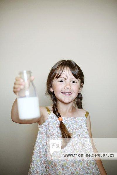 Ein kleines Mädchen mit einer Flasche Milch. Ein kleines Mädchen mit einer Flasche Milch.