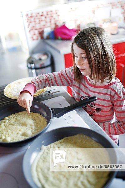 Ein kleines Mädchen macht Crêpes.