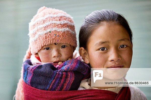 Girl carrying baby on back. Tawang  Arunachal Pradesh  India.