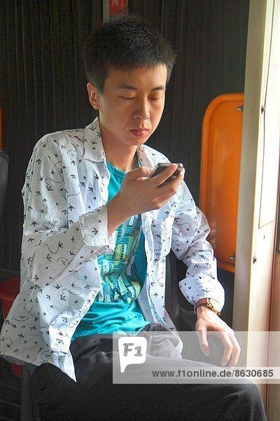 China  Beijing  Xicheng District  Guang An Men Nei Da Jie  Guanganmen Outer Street  bus  public transportation  Asian  man  sitting  passenger  rider  smartphone  looking  using  texting .