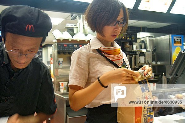 China  Hong Kong  Island  Fortress Hill  King's Road  McDonald's  fast food  restaurant  counter  manager  employee  Asian  man  woman  coworkers  uniform .
