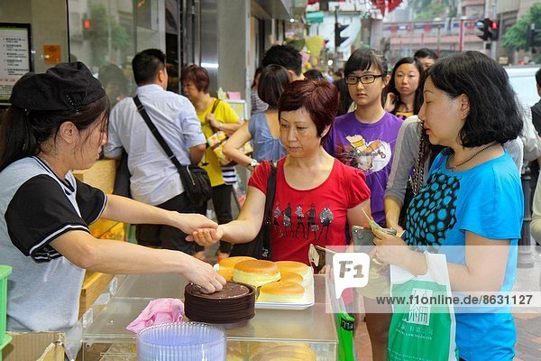 China  Hong Kong  Kowloon  Prince Edward  Prince Edward Road  bakery  sidewalk street vendor  cakes  sale  Asian  woman  buying  selling .
