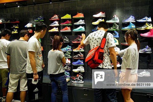 China  Hong Kong  Kowloon  Mong Kok  Fa Yuen Street  Sneaker Street  shopping  fashion  athletic shoe store  inside  sale  display  Asian  teen  boy  man  girl  woman  looking .